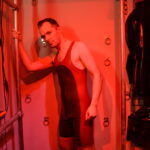 switchLDN in red and semi trans latex rubber wrestling suit in front of restraint wall with red playroom light