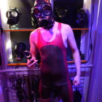 switchLDN in hooded s10 gas mask and red and semi trans latex rubber wrestling suit holding speedcuffs