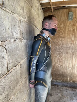 Switch chained to wall and gagged in Huub wetsuit with spiked collar - from side