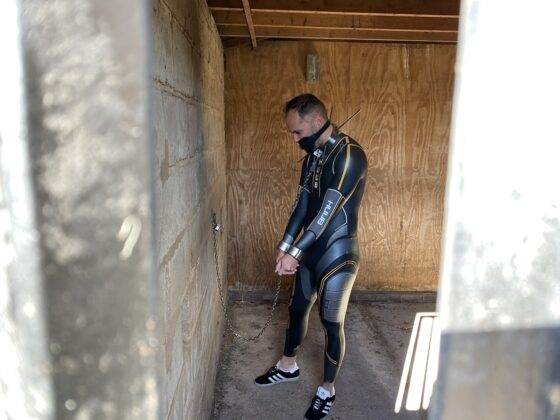 Switch cuffed to wall in Huub wetsuit
